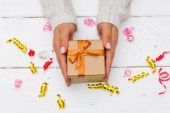 拿着在白色木桌上的女性手礼物 免版税库存照片
