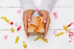 拿着在白色木背景的女性手礼物 免版税库存照片