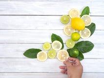 拿着在白色桌上的妇女新鲜的柠檬 免版税库存照片