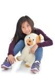 拿着在白色的亚裔女孩小狗玩偶 库存图片