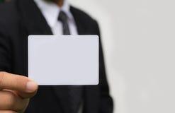 拿着在白色的商人的手白色卡片 免版税库存图片