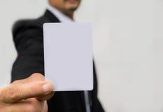 拿着在白色的商人的手白色卡片 库存照片