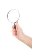 拿着在白色的女性手放大镜 库存图片