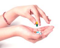 拿着在白色的手药物 免版税库存图片