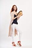 拿着在白色的年轻美丽的妇女一个帽子隔绝了背景,在充分的成长,时尚,秀丽的照片 免版税库存图片
