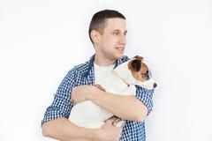 拿着在白色背景的一微笑的帅哥一条纯血统狗 人和动物的概念 拿着他的狗的年轻人 库存照片