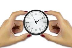 拿着在白色背景的两只女性手一个时钟保留时间c 免版税库存照片