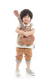 拿着在白色背景的亚裔孩子尤克里里琴被隔绝 库存图片