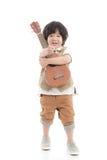 拿着在白色背景的亚裔孩子尤克里里琴被隔绝 免版税库存照片