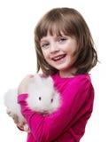 拿着一只小的白色兔子的小女孩 免版税库存图片