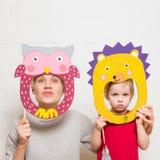 拿着在白色背景的小女孩和母亲狮子面具 免版税库存照片