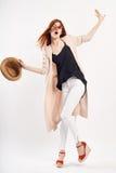 拿着在白色背景,全长,时尚的年轻美丽的妇女一个帽子 库存图片