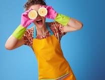拿着在眼睛前面的微笑的主妇半柠檬在蓝色 免版税库存图片