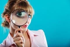 拿着在眼睛的妇女手放大镜 库存照片