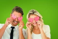 拿着在眼睛的有吸引力的年轻夫妇的综合图象桃红色心脏 免版税库存图片