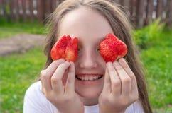 拿着在眼睛的美丽的少女草莓 免版税库存图片