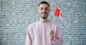 拿着在砖墙背景的快乐的学生画象加拿大旗子 股票录像