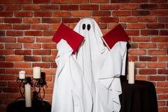 拿着在砖背景的鬼魂书 万圣节当事人 免版税库存图片