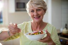 拿着在碗的资深妇女菜沙拉 免版税图库摄影
