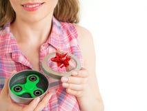 拿着在礼物盒的女孩一个五颜六色的手坐立不安锭床工人玩具 免版税库存图片