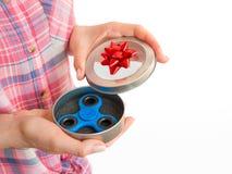 拿着在礼物盒的女孩一个五颜六色的手坐立不安锭床工人玩具 图库摄影