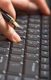 拿着在笔的手指关键董事会 免版税库存照片