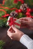 拿着在箱子的美好的女性手一个圣诞节礼物有红色弓的 库存照片