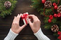 拿着在箱子的美好的女性手一个圣诞节礼物有红色弓的 库存图片