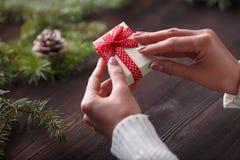 拿着在箱子的美好的女性手一个圣诞节礼物有红色弓的 免版税库存照片