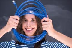 拿着在粉笔画板前面的妇女一互联网缆绳 图库摄影