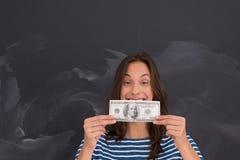 拿着在粉笔画板前面的妇女一张钞票 库存照片