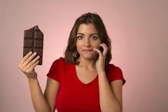 拿着在糖瘾诱惑的年轻美丽的愉快和激动的妇女大巧克力块 图库摄影