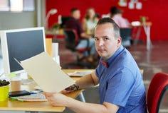 拿着在红色创造性的办公室空间的确信的男性设计师一个文件夹 免版税库存图片