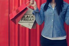 拿着在红色墙壁购物中心的妇女黑星期五购物袋 免版税库存照片