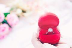 拿着在红色箱子、婚礼或者订婚概念的妇女手婚戒 免版税库存图片