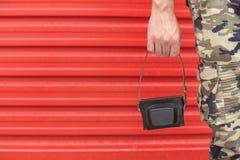 拿着在红色背景的军用长裤的人减速火箭的照相机盒 复制的空间 免版税库存图片