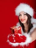 拿着在红色背景的圣诞老人帽子的女孩礼物盒。 免版税库存图片