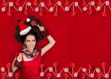 拿着在红色背景的愉快的圣诞节女孩一个棒棒糖 免版税图库摄影
