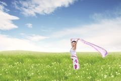 拿着在绿色草甸的无忧无虑的美丽的亚裔妇女织品 免版税库存照片