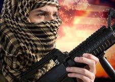 拿着在美国国旗前面的战士一个武器 库存图片