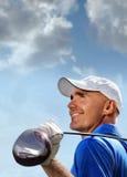 拿着在肩膀的微笑的高尔夫球运动员高尔夫俱乐部 免版税库存照片