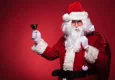 拿着在肩膀的袋子和在他的右手的圣诞老人响铃 免版税图库摄影