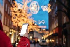 拿着在背景焕发bokeh圣诞节的人一个智能手机我 免版税库存图片