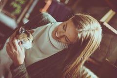 拿着在胳膊的微笑的少妇猫宠物 库存图片