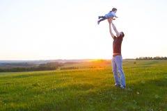 拿着在胳膊的愉快的父亲孩子,空气的投掷的婴孩 免版税库存照片