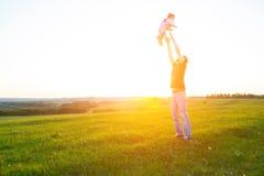 拿着在胳膊的愉快的父亲孩子,空气的投掷的婴孩 免版税库存图片