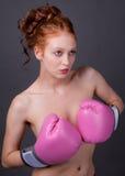 拿着在胸口前面的妇女桃红色拳击手套 库存图片