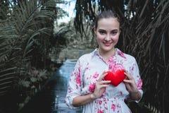 拿着在胸口的少妇红色心脏本质上 爱标志symb 免版税库存照片