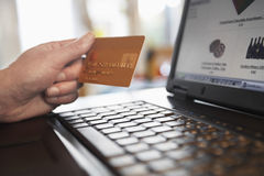拿着在膝上型计算机前面的手信用卡 免版税库存图片