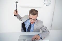 拿着在膝上型计算机的恼怒的商人锤子 免版税图库摄影